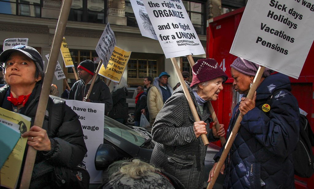 """Lallan Schoenstein, left center, trades impassioned remarks with her friend at the International Working Women's Day Rally at the Triangle Shirtwaist Fire Factory Memorial at 23 Washington Place, Manhattan, on March 8, 2014. Schoenstein, 73, said the rally gave her a """"chance to express solidarity with women around the world, particularly, women in the workforce."""""""